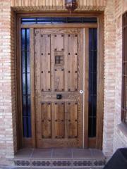 Puerta de entrada en pino teñida en nogal, modelo tablas tipo posada, con dos muros y montante fijos, reja de ...