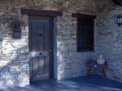 Puerta de calle en iroko, hoja modelo tablas a dos caras, con ventanillo, herrajes de seguridad, clavos negros, ...