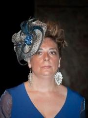 Tocado en rafia con pluma azul,y lazo trabajado en ciculo de diferente tonos azules