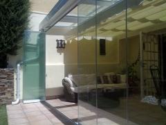 Porche con techo móvil, cortina de cristal y toldo plano