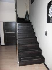 Escalera de madera de roble tinta con perfileria anti desgaste de acero sobre estructura de hormigon