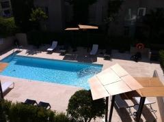 Decoracion de piscina con mobiliario, parasoles