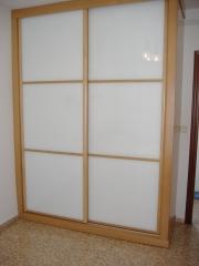 Armario empotrado: Puertas de cristal blanco enmarcadas con perfil roble