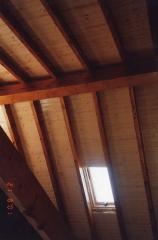 Techo de madera con ventanas en casa de obra