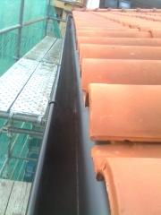 Detalle de canalón de chapa lacado en marrón con teja mixta roja
