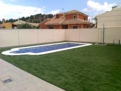 Piscina de obra con spa y terraza en cesped artificial