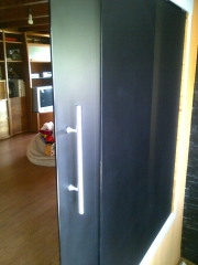 Puerta corredera de vidrio mate negro temprado tirador de acero inox.