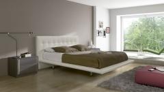 Cama tapizada en color claro del dormitorio doce