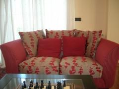 Sofa tapizado combinado y visillos con lunares.