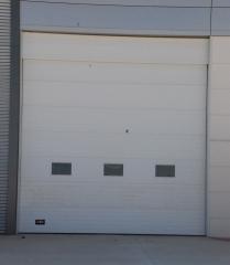 Puerta seccional industrial blanca con ventanillos