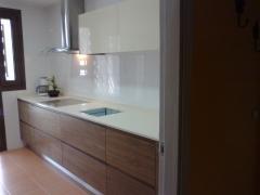 Muebles bajos barnizados nogal con fresado en puerta, sin tirador.
