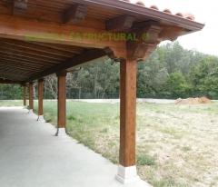 Porche a 3 aguas, con cubierta de teja mixta. con pilares de madera sobre basas de granito.