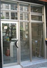 Puerta de comunidad en aluminio inox con travesa�os reforzados y vidrio de seguridad laminar.