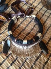 Gargantilla elaborada con cord�n marr�n de 10mm, flecos y �gatas. cierra con un atractivo lazo.