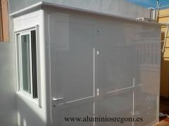 Cerramiento de aluminio blanco de panel sandwich con 1 puerta de 1 hoja abatible y una ventana