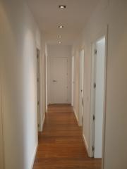 Pasillo con tarima, pintura liso, puertas lacadas en blanco y halogenos