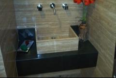 Encimera de baño en pizarra negra con lavamanos de travertino romano