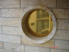 Fachada con ventana redonda en travertino