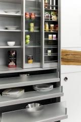 Armario despensa de cocina con puertas correderas y estanterias especieros deslizables en dos diferentes niveles.