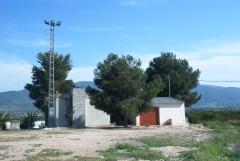 Alumbrado exterior con torre presilla y proyectores industriales de una campa junto a caseta de riegos agricolas.