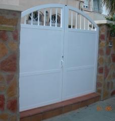 Puerta de aluminio de 2 hojas abatibles con parte alta de medio punto, barrotes redondos, panel sandwich ...