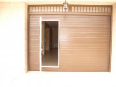 Puerta seccional con una puerta peatonal incorporada.