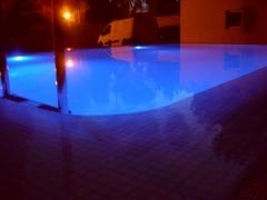 Iluminacion con luces de leds en piscina desbordante con gresite blanco perla