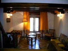 Amplio salón con doble altura, escaleras de madera, en ambiente rústico