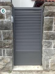 Puerta peatonal trabajada en perfileria inclinada para dejar paso de aire pero evitar la vision interior