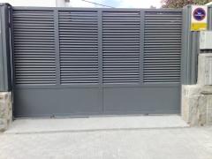 Puerta corredera trabajada en perfileria inclinada para dejar paso de aire pero evitar la vision interior