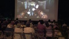 Proyecci�n de cine en tres dimensiones al aire libre.  proyector de gran potencia. gafas 3d de cartoncillo blanco. ...