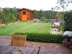 Pequeño jardin con pradera separada por traviesas de ferrocarril  de la zona de arbustos para que el césped no la ...