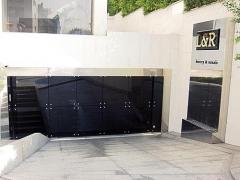 Puerta batiente autom�tica de dos hojas con vidrio de seguridad antimot�n negro + inox.