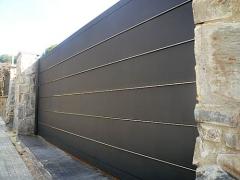 Puerta corredera autom�tica residencial fabricada con bandejas horizontales de acero galva. + inox.