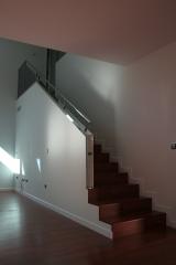 Escalera revestida con tarima igual que el suelo y barandilla inox.